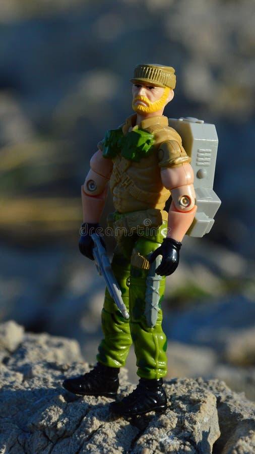 Spielzeugfigur der GI Joe-Serie namens Rock N' Roll auf Küstensteinen mit Gewehrmodell in der linken Hand lizenzfreie stockbilder