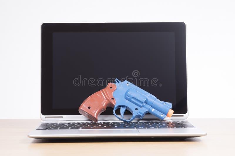Spielzeuggewehr gesützt auf einer Laptop-Computer lizenzfreie stockbilder