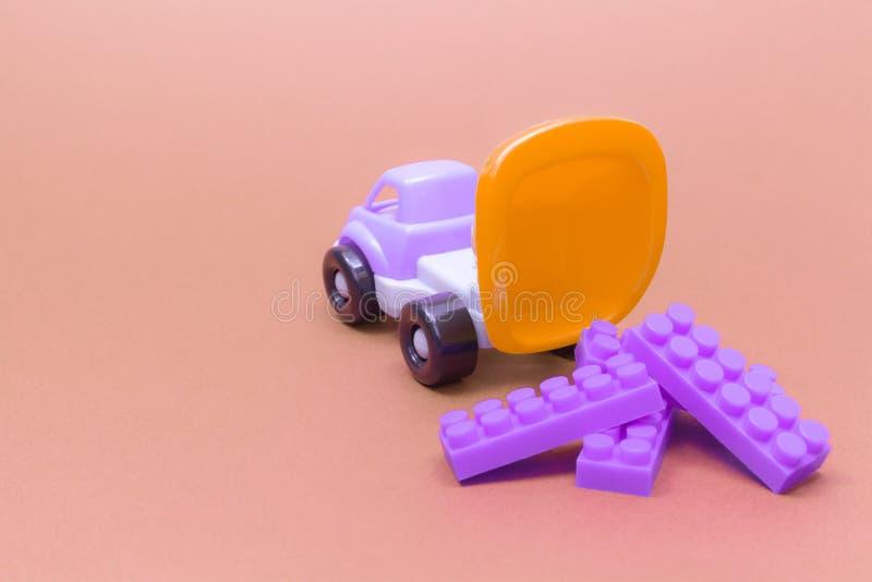 Spielzeuglastwagen entlädt die Details der Blöcke auf einem rosa Hintergrund lizenzfreies stockbild