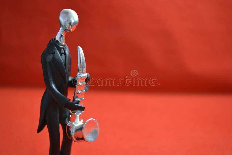 Spielzeugmann mit saxaphone auf rotem Hintergrund lizenzfreie stockfotos
