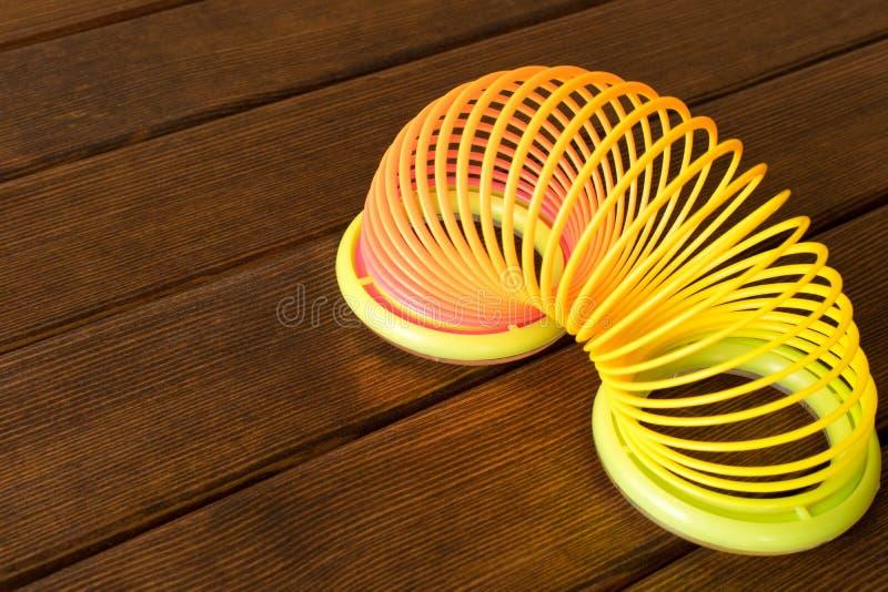 Spielzeugplastikregenbogen auf einem Holztisch Mehrfarbige Spirale für lizenzfreies stockfoto