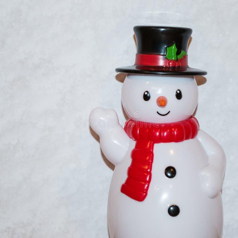 Spielzeugschneemann, der mit weißem Schal und schwarzem Zylinder mit roter Schärpe wellenartig bewegt lizenzfreie stockbilder