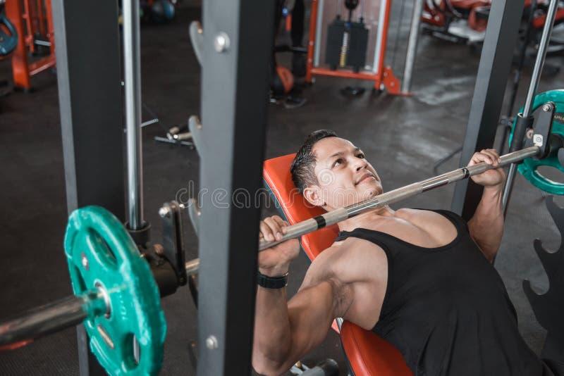 Spier de perstraining van de bodybuilderbank met de machine van Smith stock afbeelding