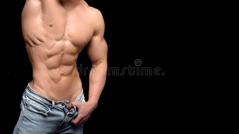Spier en sexy torso van jonge sportieve mensenbodybuilder in jeans met perfecte abs, bicep en borst royalty-vrije stock afbeeldingen
