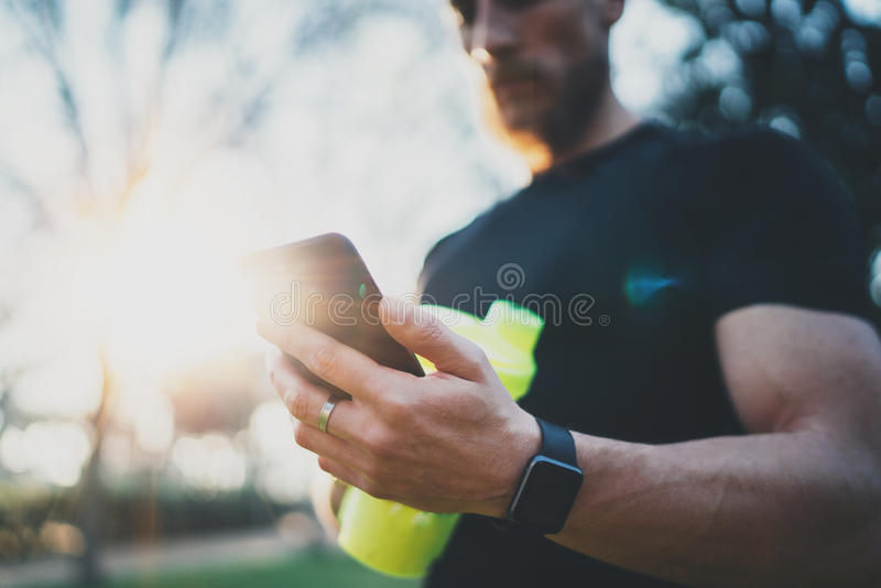 Spier gebaarde atleet die gebrande calorieën controleren op smartphonetoepassing na goede training openluchtzitting over stad stock fotografie