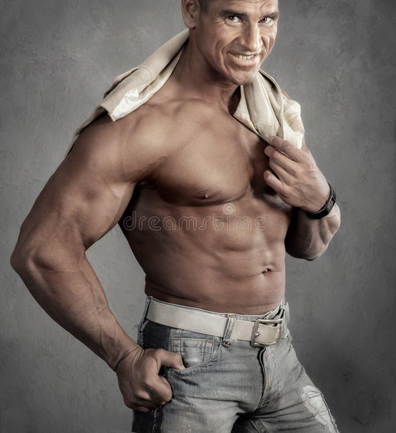 Spier glimlachende shirtless mens tegen grijze achtergrond royalty-vrije stock afbeeldingen