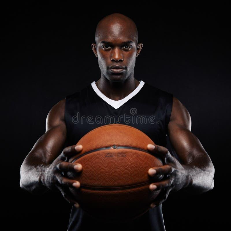 Spier jonge basketbalspeler met een bal royalty-vrije stock afbeelding