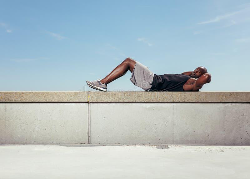 Spier jonge mens die zitten-UPS doen royalty-vrije stock afbeelding