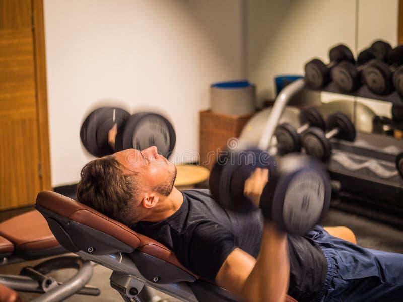 Spier jonge mens, opleiding Pecs op gymnastiekbank stock fotografie