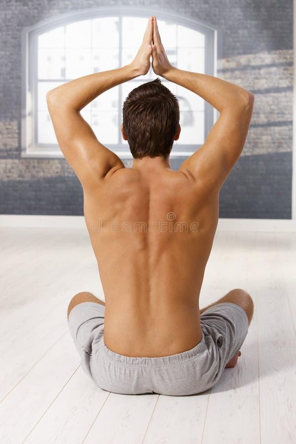 Spier jonge mens in yogaoefening royalty-vrije stock fotografie