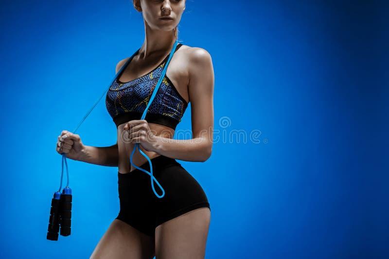Spier jonge vrouwenatleet met een touwtjespringen op blauw stock afbeeldingen