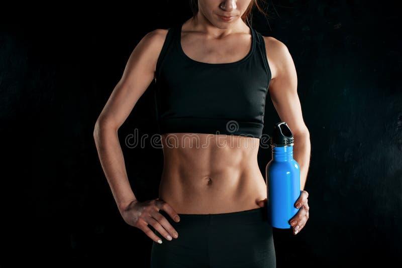 Spier jonge vrouwenatleet met een water op zwarte royalty-vrije stock foto