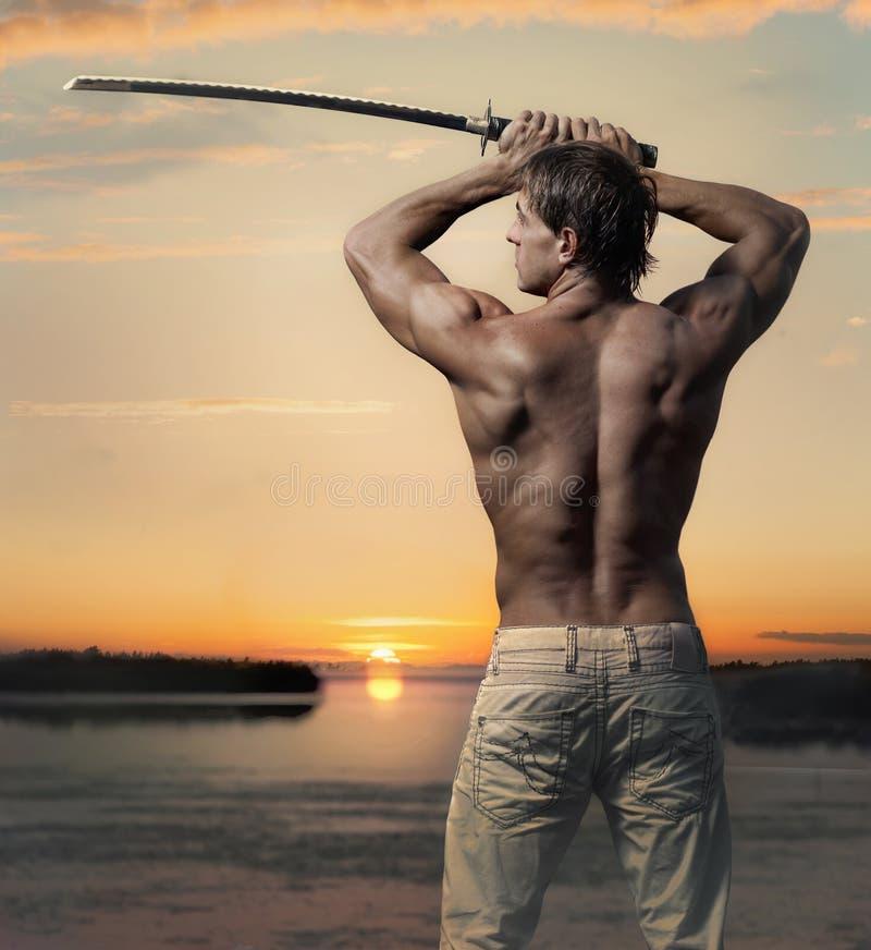 Spier knappe kerel met zwaard bij zonsondergang royalty-vrije stock afbeelding