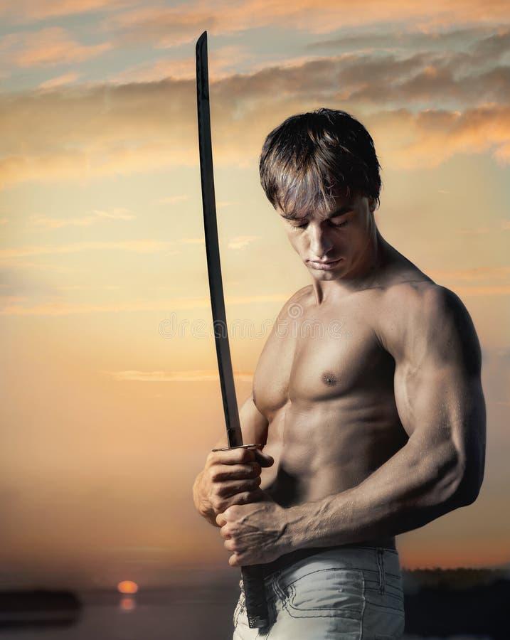 Spier knappe kerel met zwaard bij zonsondergang stock foto's