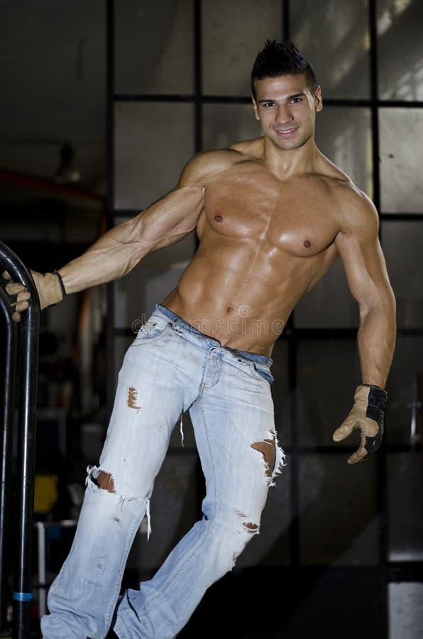 Spier latino bodybuilder in jeans die van metaalhandvat hangen stock afbeelding