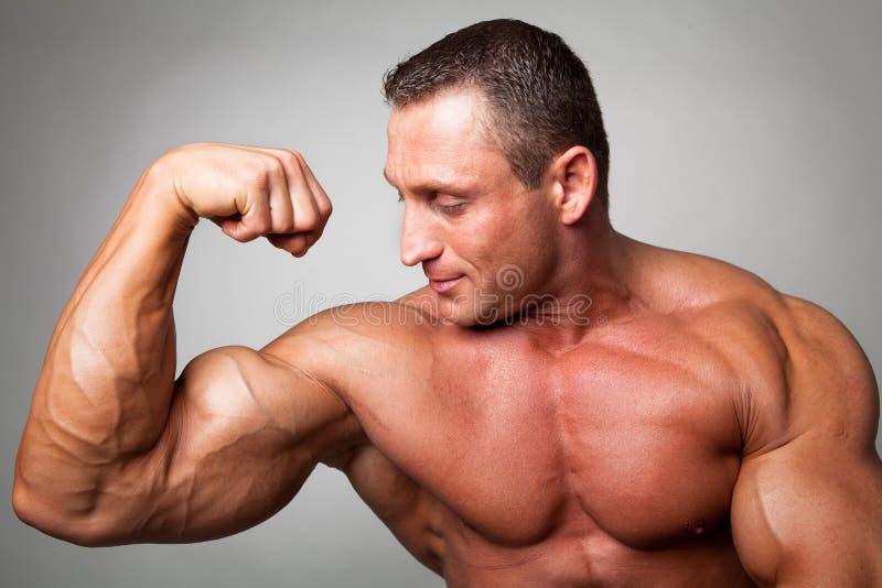 Spier mens die zijn bicepsen buigt royalty-vrije stock foto