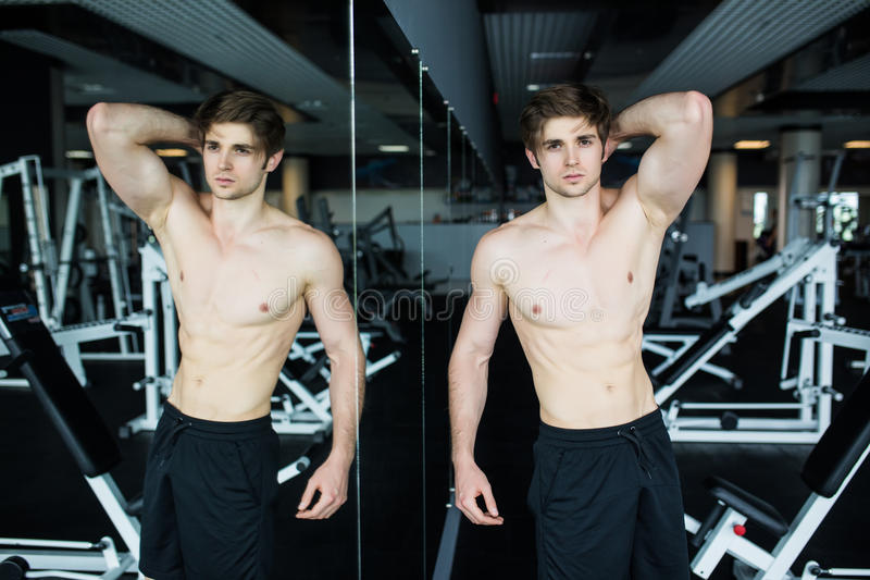 Spier, shirtless jonge mens die in gymnastiek tijdens training rusten, die spiertorso, Pecs en abs in de spiegel tonen bij gymnas royalty-vrije stock fotografie