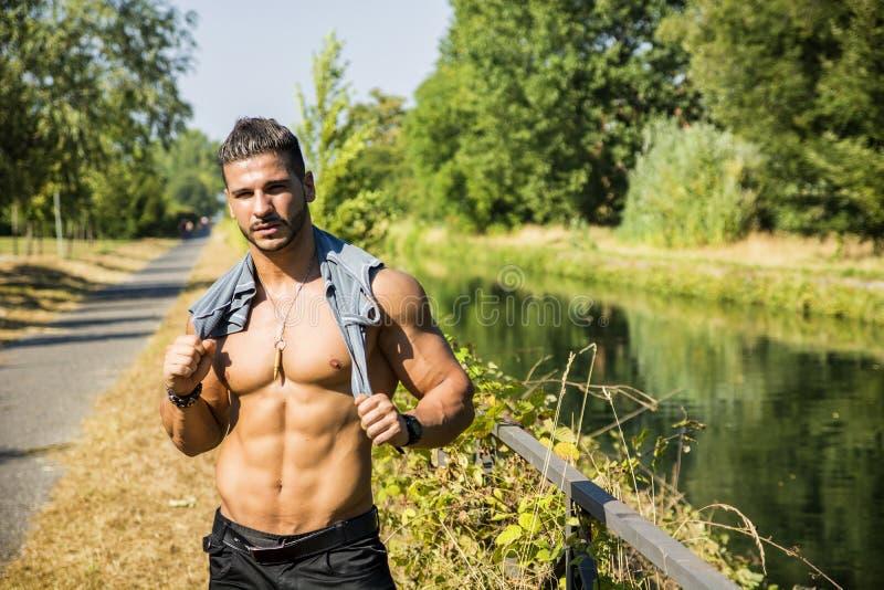 Spier shirtless mens openlucht door kleine rivier stock foto's