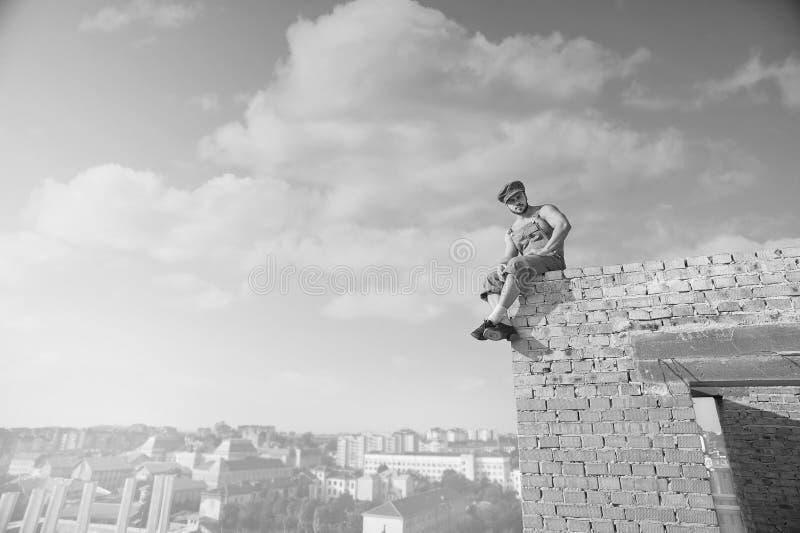 Spier shirtless retro bouwer bovenop een bakstenen muur royalty-vrije stock foto