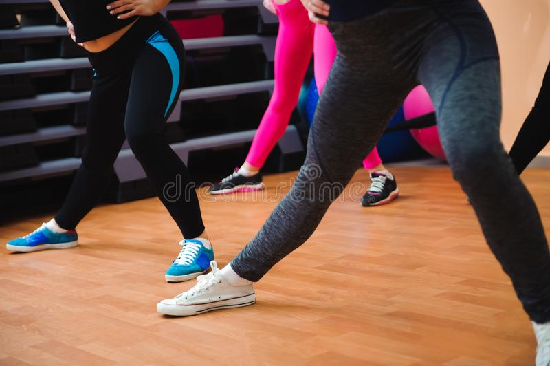 Spier vrouwelijke benen bij geschiktheid de opleiding Mooie vrouwen die aerobics in geschiktheidsclub uitoefenen stock fotografie