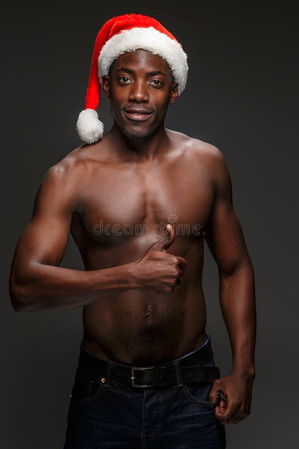 Spier zwarte shirtless jonge mens in Santa Claus-hoed royalty-vrije stock afbeelding
