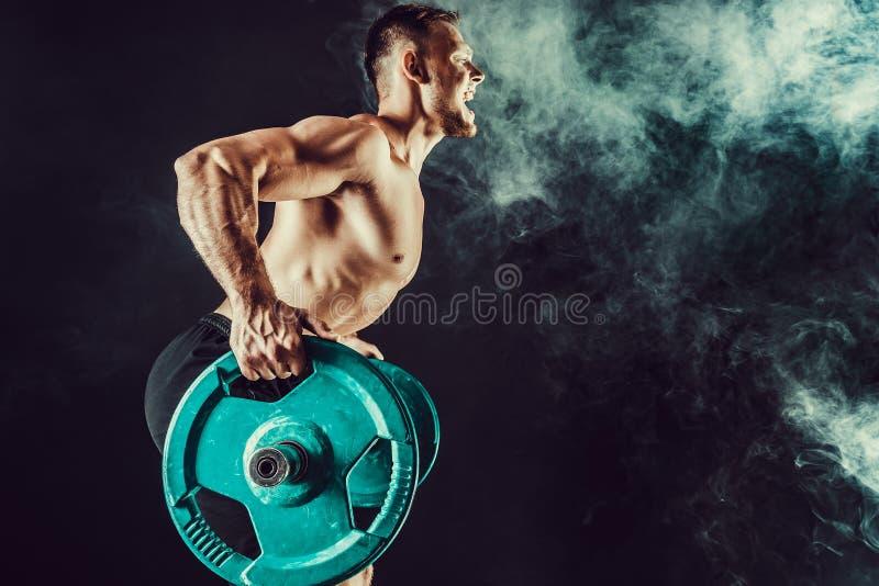 Spierbodybuilder knappe mensen die oefening doen stock afbeeldingen