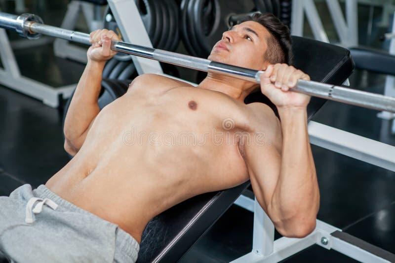 Spierbodybuilderkerel die het opheffen gewicht doen terwijl het uitwerken stock foto's