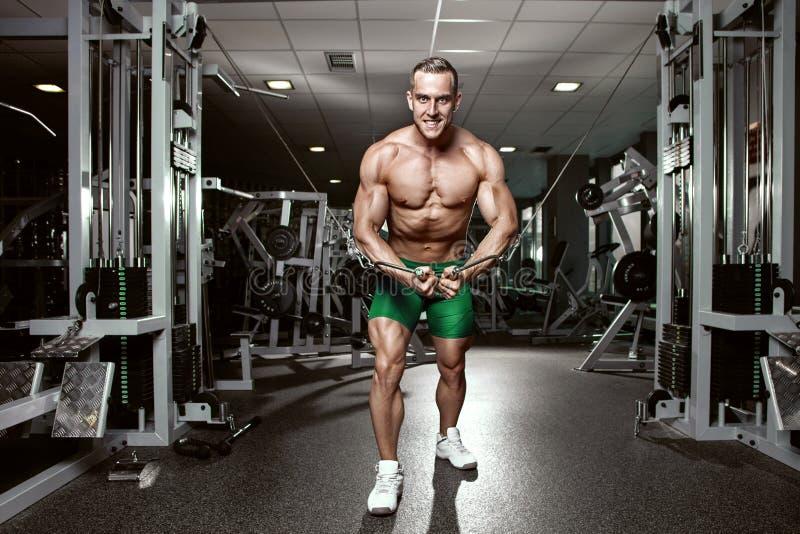 Spierbodybuilderkerel die oefeningentraining in gymnastiek doen stock fotografie