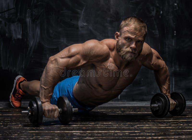 Spierbodybuilderkerel over donkere achtergrond stock fotografie