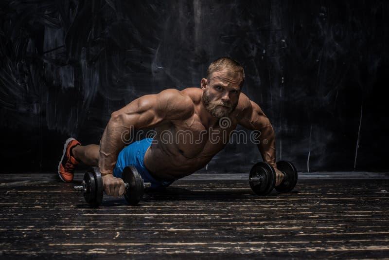 Spierbodybuilderkerel over donkere achtergrond stock afbeeldingen