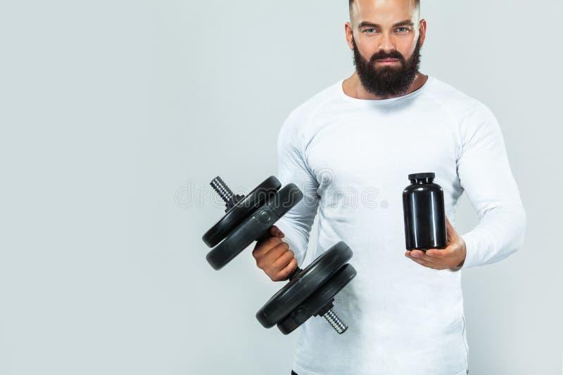 Spierfitness sportenmens met een kruik sportenvoeding - proteïne, gainer en caseïne stock foto