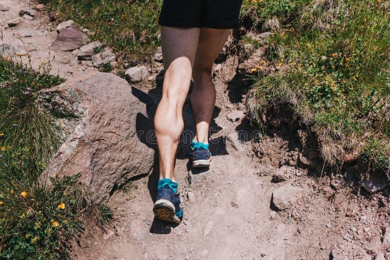 Spierkalveren van een jonge atleet die een bergweg, u lanceren stock afbeelding