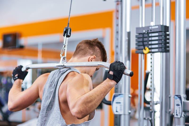 Spierlichaams bouwmensen die zijn rug opleiden bij de gymnastiek stock afbeelding