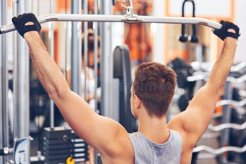 Spierlichaams bouwmensen die zijn rug opleiden bij de gymnastiek stock foto's