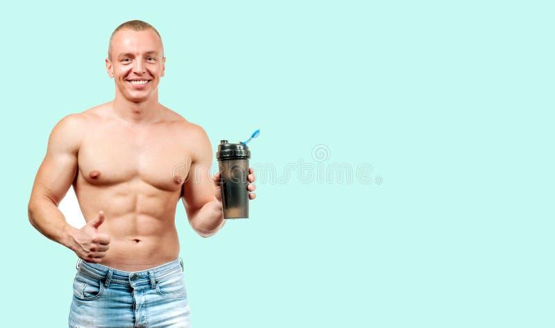 Spiermens die eiwitsportenvoeding op groene achtergrond nemen stock afbeelding