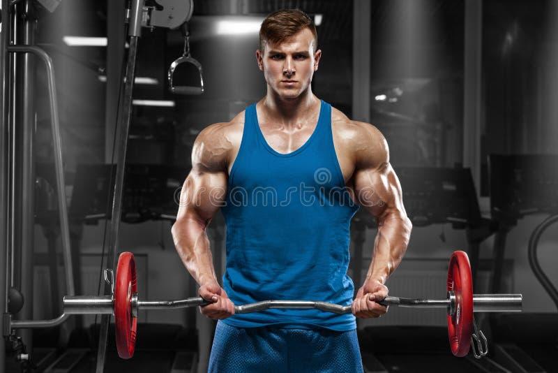 Spiermens die in gymnastiek uitwerken die oefeningen met barbell doen bij bicepsen, sterk mannetje stock foto
