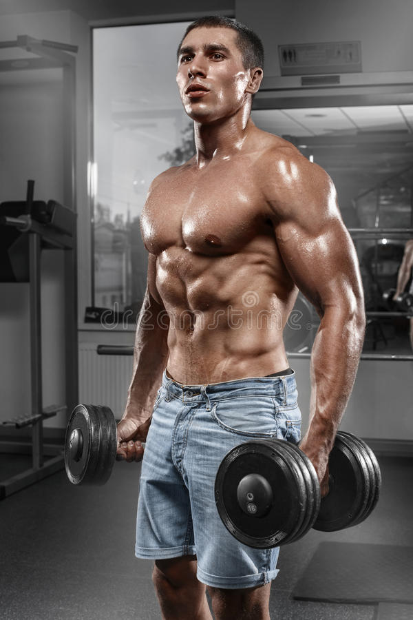 Spiermens die in gymnastiek uitwerken die oefeningen met barbell, sterke mannelijke naakte torsoabs doen stock foto's