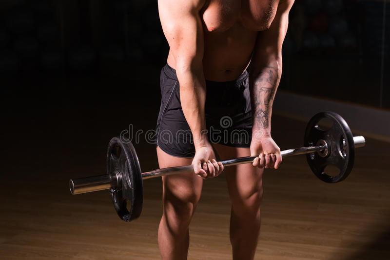 Spiermens die in gymnastiek uitwerken die oefeningen met barbellclose-up doen, sterke mannelijke naakte torsoabs stock foto's