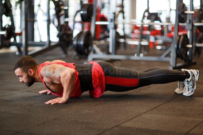 Spiermens die in gymnastiek uitwerken die oefeningen doen stock afbeelding