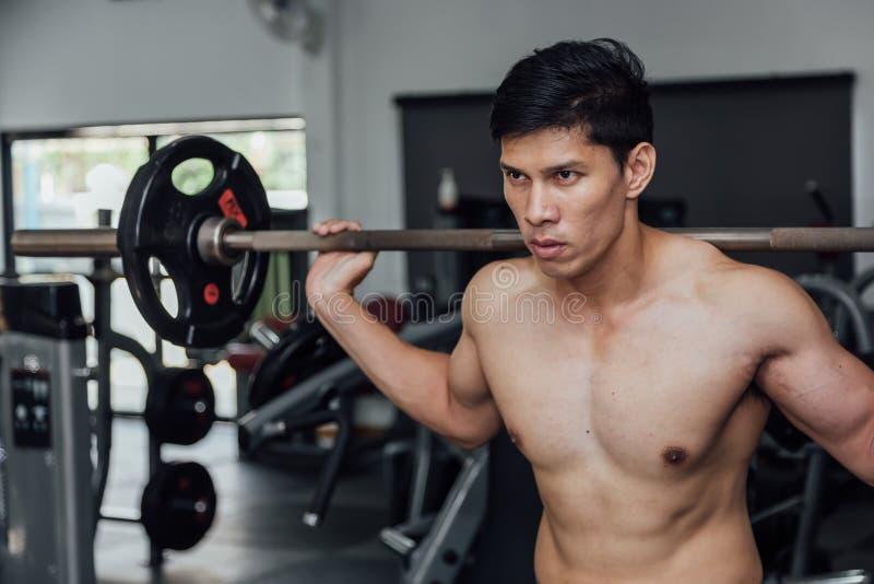 Spiermens die in gymnastiek uitwerken die oefeningen met barbell doen bij bicepsen, sterk mannetje royalty-vrije stock afbeeldingen