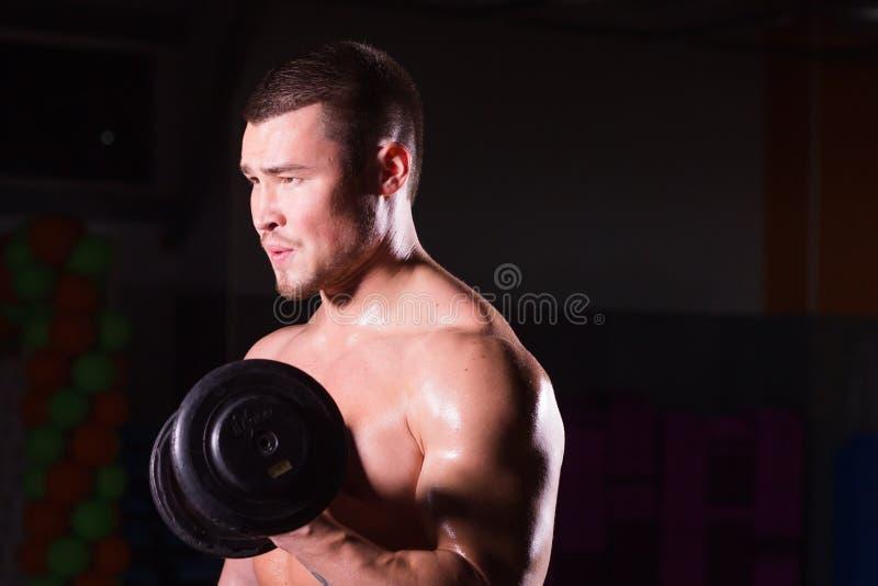 Spiermens die in gymnastiek uitwerken die oefeningen met domoren doen bij bicepsen, sterke mannelijke naakte torsoabs royalty-vrije stock foto