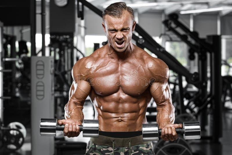 Spiermens die in gymnastiek uitwerken die oefeningen voor bicepsen, sterke mannelijke naakte torsoabs doen royalty-vrije stock afbeelding