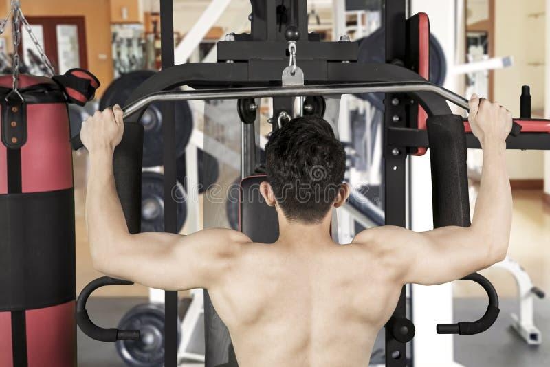 Spiermens die training met geschiktheidsmachine doen royalty-vrije stock afbeelding