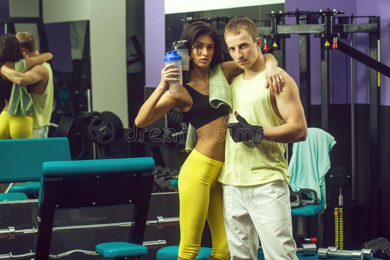 Spiermens en sexy meisje bij gymnastiektrainer met fles royalty-vrije stock foto