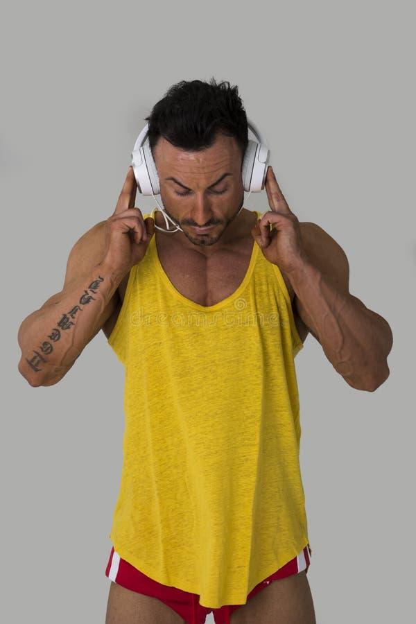 Spiermens status, die aan muziek op hoofdtelefoons luisteren stock fotografie