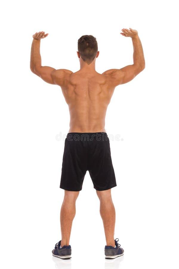 Spiermensenholding iets over Zijn Hoofd stock fotografie
