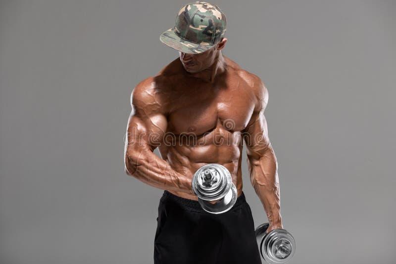 Spiermensentraining die oefeningen met domoren voor bicepsen doen, die op de grijze achtergrond worden ge?soleerd Sterke mannelij stock fotografie