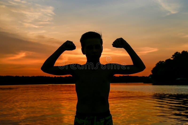 Spiersilhouet van jongen bij meer tijdens zonsondergang stock afbeelding