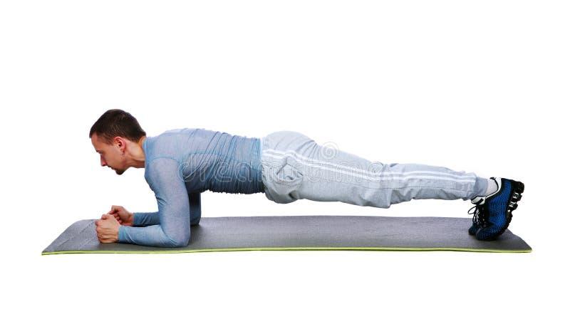 Spiersportman het praktizeren yoga op een mat stock afbeeldingen