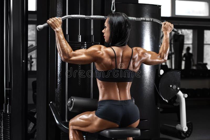 Spiervrouw die in gymnastiek uitwerken die oefening voor rug doen Sterk geschiktheidsmeisje, spieren achter stock fotografie